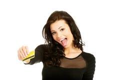 Hållande kreditkort för lycklig gladlynt kvinna royaltyfri foto