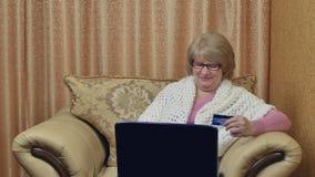 Hållande kreditkort för lycklig kvinna som gör online-shopping En kvinna som använder en bärbar dator, gör köp i ett online-lager stock video