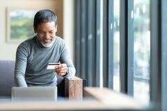 Hållande kreditkort för lycklig mogen man som direktanslutet betalar, genom att använda bärbara datorn för betalning Asiatisk hög arkivfoton