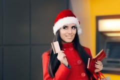 Hållande kreditkort för lycklig shoppingkvinna som är främst av en ATM Royaltyfri Fotografi