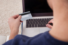 Hållande kreditkort för person genom att använda bärbara datorn Arkivfoto