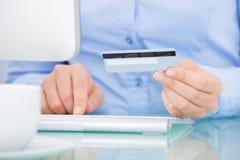 Hållande kreditkort för person genom att använda datoren Royaltyfria Bilder