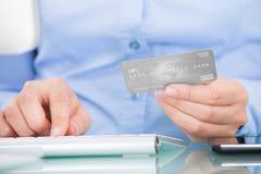 Hållande kreditkort för person genom att använda datoren Royaltyfria Foton