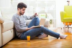 Hållande kreditkort för stilig man och användabärbar dator för online-shopping Arkivbild
