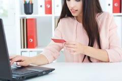 Hållande kreditkort för ung kvinna i hand och skrivande in säkerhetskod genom att använda bärbar datortangentbordet arkivbilder
