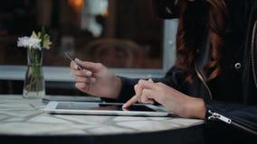 Hållande kreditkort för ung kvinna och använda bärbar datordatoren Online-shoppingbegrepp i lycklig brunettflicka för modernt kaf arkivfilmer