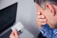 Hållande kreditkort för uppriven man Arkivbild