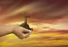Hållande kristenkors för mänsklig hand med jord på handen Royaltyfri Foto