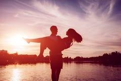Hållande kvinna för ung man på sommarflodbanken Par som har gyckel på solnedgången Kyla för grabbar royaltyfria foton