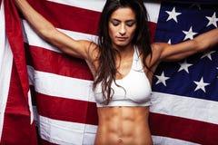 Hållande landsflagga för kvinnlig idrottsman nen proudly Royaltyfri Fotografi