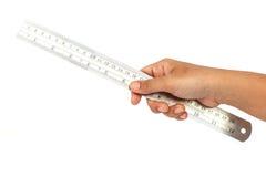 Hållande linjal för hand som isoleras på vit bakgrund Arkivfoto