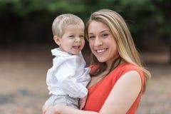 Hållande litet barnson för gullig Millennial mamma Royaltyfri Fotografi