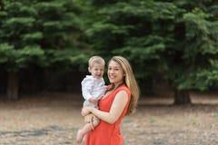 Hållande litet barnson för gullig Millennial mamma Royaltyfri Bild