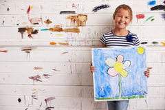 Hållande målning för flicka mot den dolda väggen för målarfärg i studio arkivfoto
