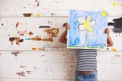 Hållande målning för flicka mot den dolda väggen för målarfärg i studio arkivbild
