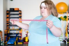 Hållande måttband för sjukligt fet kvinna royaltyfri foto
