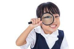 Hållande magnifyin för lycklig asiatisk kinesisk liten grundskola för barn mellan 5 och 11 årflicka Arkivfoto