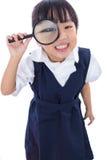 Hållande magnifyin för lycklig asiatisk kinesisk liten grundskola för barn mellan 5 och 11 årflicka Arkivfoton