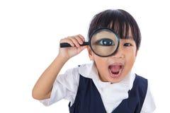 Hållande magnifyin för lycklig asiatisk kinesisk liten grundskola för barn mellan 5 och 11 årflicka Arkivbilder