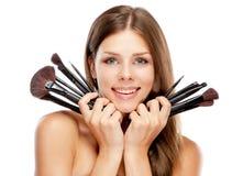Hållande makeupborstar för härlig kvinna Arkivfoto