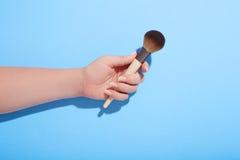 Hållande makeupborste för kvinna i hennes hand på blå bakgrund, bästa sikt Royaltyfri Foto