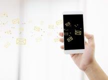 Hållande mankontroll för hand och överföringsmeddelande med emailen i en telefon Arkivfoto