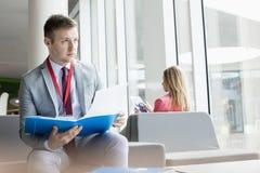 Hållande mapp för fundersam affärsman, medan sitta på lobbyen i konventcentrum royaltyfria foton