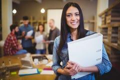 Hållande mapp för säker affärskvinna medan kollegor i bakgrund Royaltyfri Foto