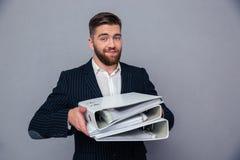 Hållande mappar för lycklig affärsman arkivfoto