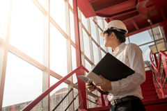 Hållande mappar för ung asiatisk tekniker på konstruktionsplatsen Royaltyfri Bild