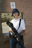 Hållande maskingevär för kvinna på skjutavstånd Royaltyfri Foto