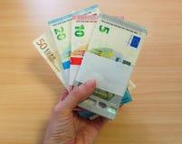 Hållande massor för hand av pengar arkivfoto