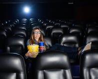 Hållande mellanmål för kvinna, medan hålla ögonen på filmen 3D på Royaltyfria Foton