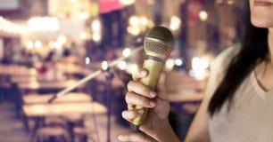 Hållande mikrofon för kvinna i hand på bar och restaurang arkivfoto