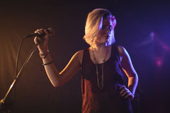 Hållande mikrofon för kvinnlig sångare i upplyst nattklubb Arkivfoton