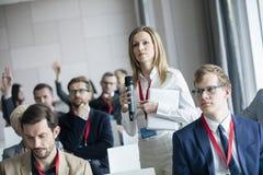 Hållande mikrofon för säker affärskvinna, medan fråga frågor under seminarium Arkivbilder