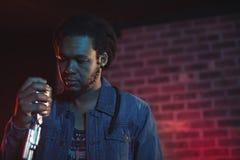 Hållande mikrofon för säker manlig sångare i nattklubb Royaltyfria Bilder