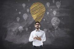 Hållande minnestavla för affärsman som är främst av svart tavla med ballongen Fotografering för Bildbyråer