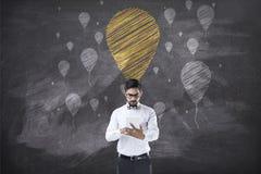 Hållande minnestavla för affärsman som är främst av svart tavla med ballongen arkivfoton