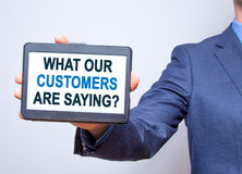 Hållande minnestavla för affärsmanhand med vad våra kunder är Sayi Arkivfoto