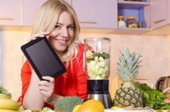Hållande minnestavla för lycklig kvinna bredvid en juicer som är full av frukt fotografering för bildbyråer