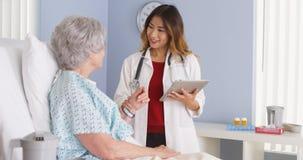 Hållande minnestavladator för japansk doktor som talar till den mogna kvinnan i sjukhussäng arkivfoton