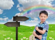 Hållande minnestavladator för pojke i grönt fält Arkivfoton