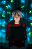 Hållande minnestavlaPC för flicka i hatt för jultomten` s Fotografering för Bildbyråer