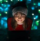 Hållande minnestavlaPC för flicka i hatt för jultomten` s Royaltyfria Bilder