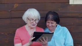 Hållande minnestavlaPC för hög kvinna i hand och använda för vän för klocka tillsammans arkivfilmer
