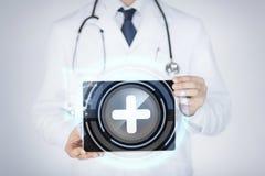 Hållande minnestavlaPC för manlig doktor med läkarundersökningen app Arkivbild