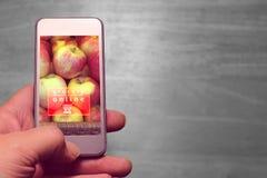 Hållande mobil för hand och livsmedelsbutikonline-text Arkivfoton