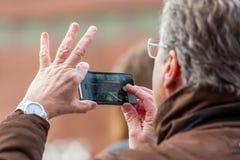 Hållande mobil pnone för hög person royaltyfri fotografi