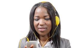 Hållande mobiltelefon för afrikansk flicka och lyssna till musik royaltyfria bilder